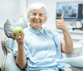 An older woman giving a thumbs up and holding an apple