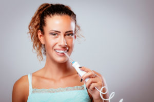 Woman with braces using water flosser